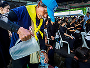 27 SEPTEMBER 2017 - BANGKOK, THAILAND:  A volunteer pours cold drinking water into a bottle for a person waiting to pay final respects to the funeral urn of the late King. The Royal Household has announced that the palace will close to the public, including tourists, on 04 October 2017 to allow officials to complete preparations for the cremation of Bhumibol Adulyadej, the King of Thailand, who died on 13 October 2016. They also extended the official mourning period by 15 days. It was originally set to end on 13 October 2017 but now will end on 26 October 2017, the day of the King's cremation.    PHOTO BY JACK KURTZ