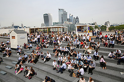 © Licensed to London News Pictures. 17/07/2019. London, UK. City workers and tourists enjoy the warm weather in the Scoop, at Moor London, near Tower Bridge at lunchtime. According to the Met Office, rain is forecast across the country during the next few days. Photo credit: Dinendra Haria/LNP