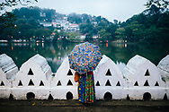 A woman in colorful dress looks out over Bogambara Lake, Kandy, Sri Lanka, Asia