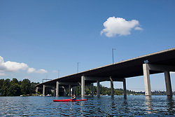 North America, United States, Washington, Bellevue, teenage boy kayaking under I90 highway bridge to Mercer Island.  MR
