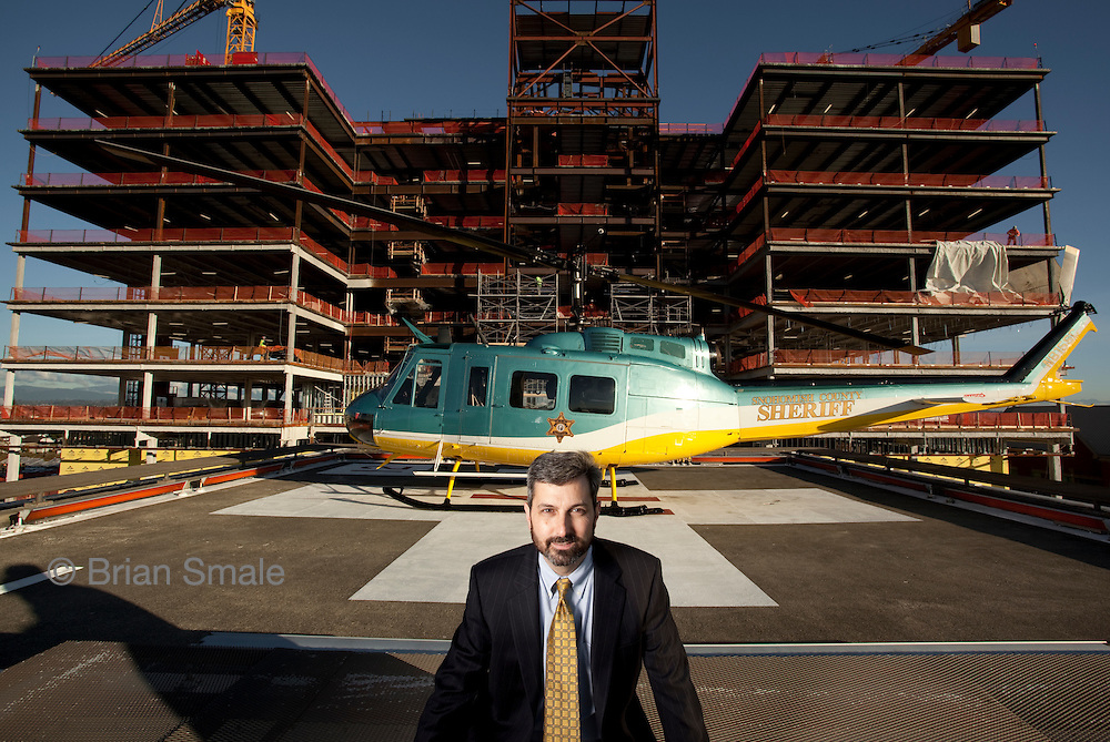 CEO Dave Brooks, on helipad of hospital.  New hospital constructino in background.