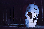 Brooklyn, NY - 17 September 2014. A giant skull by scupltor Andrew Clancy sits on a bed of stones and is surrounded by hanging loudspeakers in the Pan Pan Theatre prouction of Samuel Beckett's Embers in the Harvey Theater at the Brooklyn Academy of Music. Andrew Bennet as Harvey and Áine Ni Mhuirí as Ada speak from within the skull.