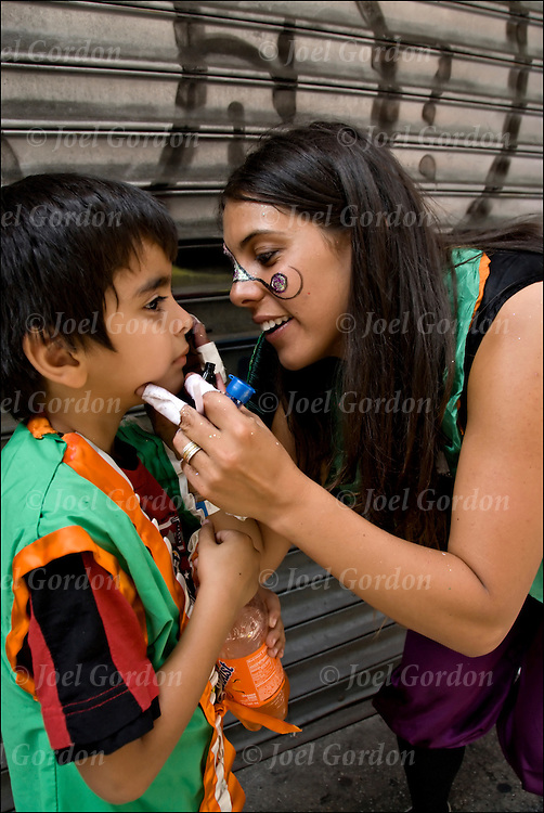 Uruguayan mother helping with make-up and face painting of son who is marching in the Dominican Day Parade in New York City.