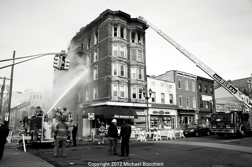 HOBOKEN, NJ - February 20:  Hoboken firefighters put water on a smoldering fire after the four-alarm fire tore through five floors of a building at 300 Washington St. on February 20, 2012 in HOBOKEN, NJ. Firefighters from Hoboken, Newark and Elizabeth battled the blaze which started at around 7 p.m. Sunday. They were still extinguishing flames from a section of the roof that was burning early Monday. Officials say three people who had been inside the building were treated for smoke inhalation.  (Photo by Michael Bocchieri/Bocchieri Archive)