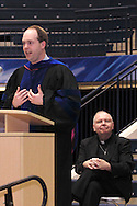 Alter president Rev. James Manning (right) watches as Archdiocese of Cincinnati superintendent Dr. Jim Rigg speaks during the 47th commencement excercise of Archbishop Alter High School at Trent Arena in Kettering, Saturday, May 26, 2012.