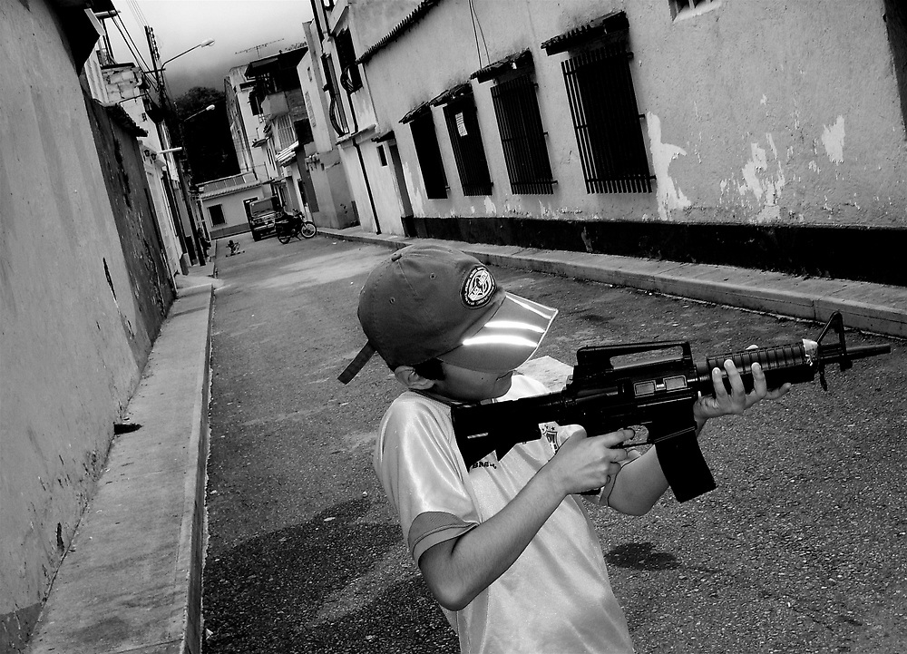Portraits of life in Belen....A child with a toy gun pretends to shoot people passing by in the streets of Belen, a red zone sector in Venezuela heavily controlled by Colombian narco-traffickers.