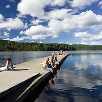 Idyllic image of young people sunbathing at Sognsvann lake, Oslo, Norway.