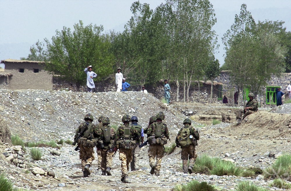 "British Royal Marine 45 Commandos move towards a local village while conducting an ""eagle vehicle check point"" (VCP) mission for Operation Buzzard July 8, 2002 in southeastern Afghanistan. During VCPs, small groups of marines are dropped quickly by helicopters to search random vehicles on dirt roads and trails near the Pakistan-Afghanistan border to deny al Qaeda and Taliban fighters freedom of movement across the region."