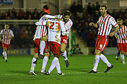 Jerome Okimo of Stevenage is mobbed after his freak wind assisted goal beats Ben Wilson (Goalkeeper) of AFC Wimbledon during the Sky Bet League 2 match between AFC Wimbledon and Stevenage at the Cherry Red Records Stadium, Kingston, England on 12 December 2015. Photo by Stuart Butcher.