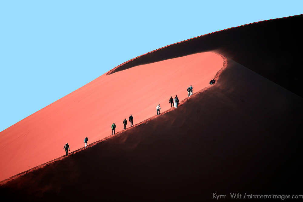 "Africa, Namibia, Sossusvlei. Visitors hike the crest of ""Big Mama"" sand dune in Sossusvlei."