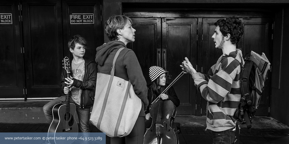 Street photography, Queen Street, Auckland, New Zealand. Young street musicians with guitar and cello. Friends or passers-by in discussion.