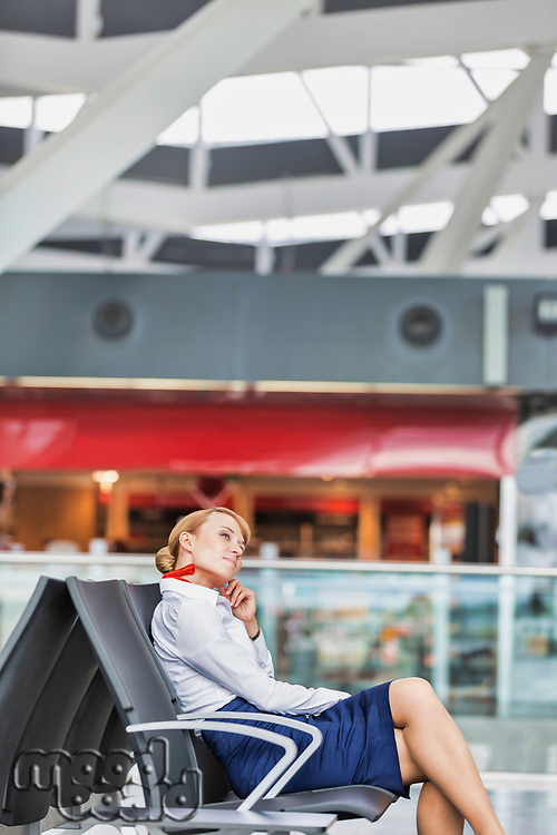 Portrait of young thoughtful attractive airport staff sitting during break