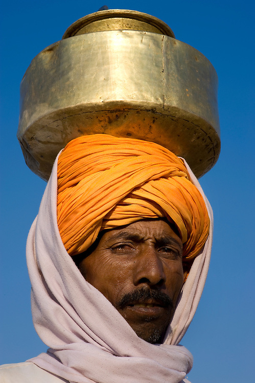 Carrying the milk in a waterpot on his head, this man sells daily at the huge cattle fair in Pushkar that is held every year in the Rajasthani Thar desert.