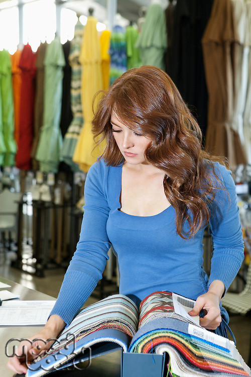 Beautiful young woman looking at textile samples in store