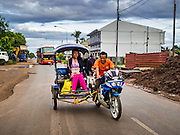 16 JUNE 2016 - PAKSE, CHAMPASAK, LAOS:  A samlor, or three wheeled taxi, takes a woman to a market in Pakse.  Lao samlors use motorcycles, but otherwise are similar to rickshaws. Pakse is the capital of Champasak province in southern Laos. It sits at the confluence of the Xe Don and Mekong Rivers. It's the gateway city to 4,000 Islands, near the border of Cambodia and the coffee growing highlands of southern Laos.      PHOTO BY JACK KURTZ
