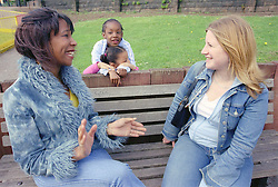 Two single mothers sitting on park bench talking with young children in background,