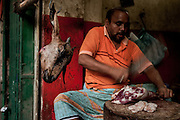A butcher prepares a leg of goat in Sadarghat.