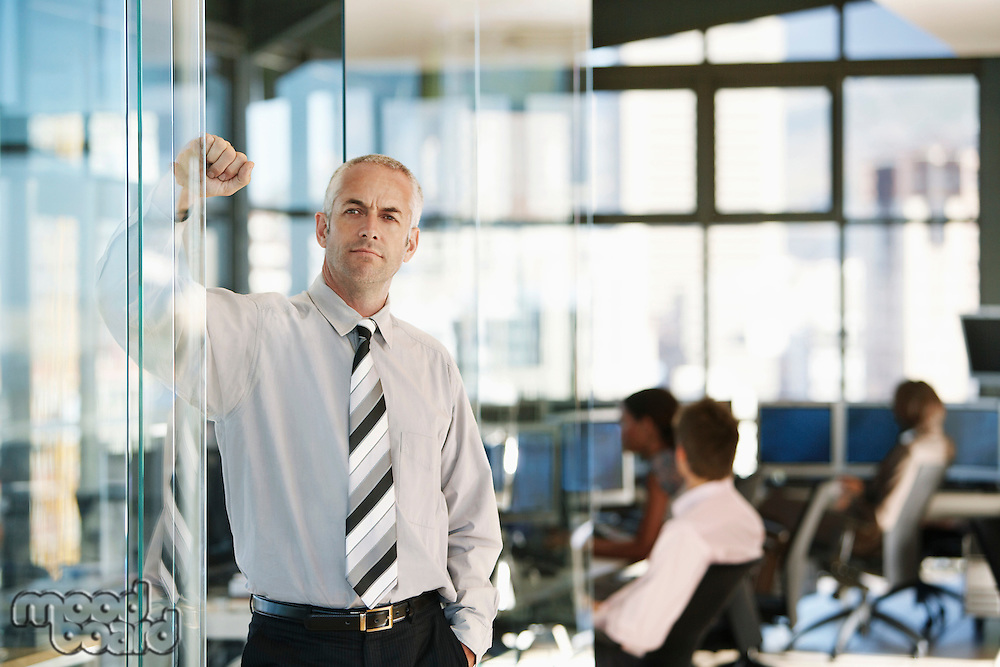 Businessman leaning on door in office with office workers in background.