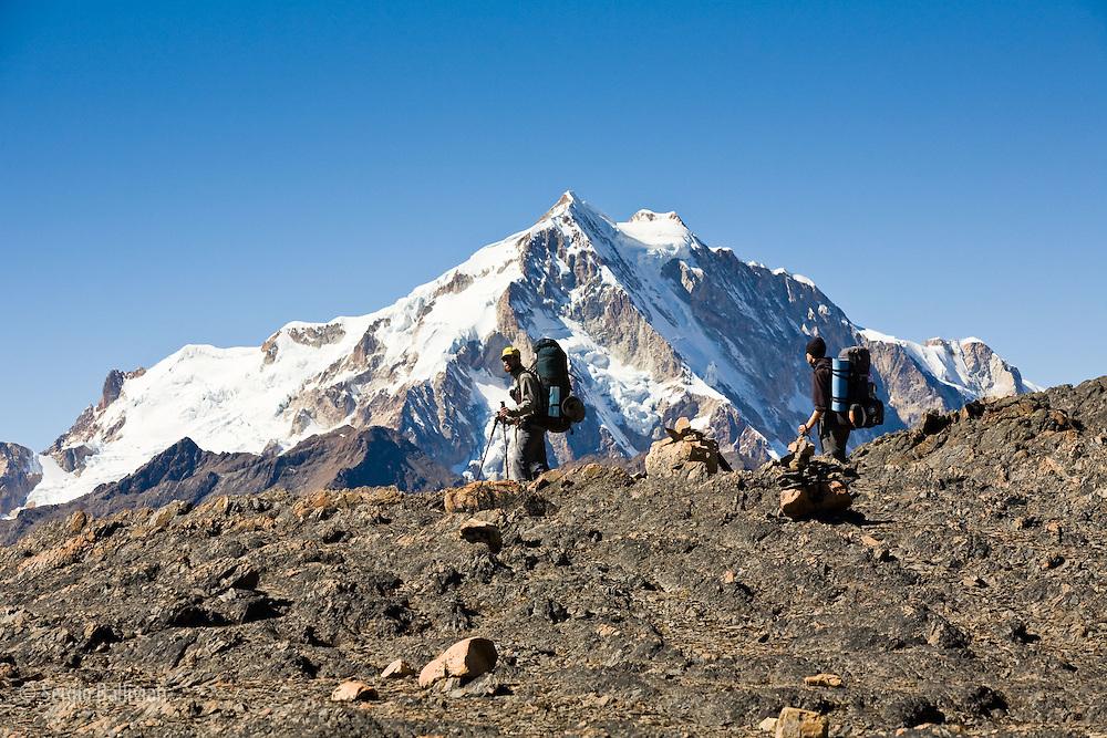 Mt. Huayna Potosi (19,975') dwarfs trekkers heading south from Condoriri to Botijlaka in Bolivia's Cordillera Real of the Andes.