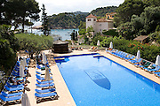 The pool at the Hotel Aigua Blava, Costa Brava, Spain. In the distance, across the bay on a bluff is the white Parador de Aigua Blava.