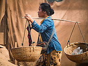 11 MARCH 2016 - LUANG PRABANG, LAOS: A vendor walks through the community of Chomphet, across the Mekong River from Luang Prabang. Laos is one of the poorest countries in Southeast Asia. Tourism and hydroelectric dams along the rivers that run through the country are driving the legal economy.       PHOTO BY JACK KURTZ