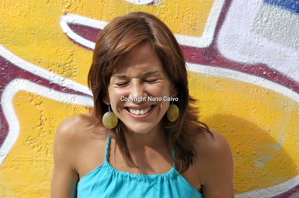 MR: Young woman in her twenties doing a funny face, with a graffitti painted wall behind