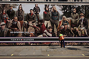 Workman sweeps beneath a billboard for clothing retailer Tommy Hilfiger showing the wealthy classes in a country setting.