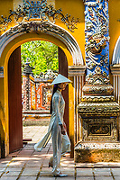 A Vietnamese woman wearing the traditional Ao Dai costume walk through the North Gate of The Imperial City, a walled palace within the citadel of the city of Huế which is the former imperial capital of Vietnam. Hue, Central Vietnam.
