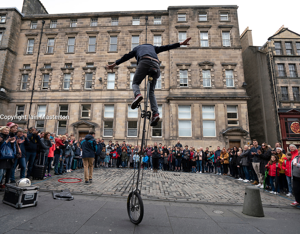 Street performer on unicycle performs to crowd on the High Street Royal Mile in Edinburgh Old Town, Scotland, UK