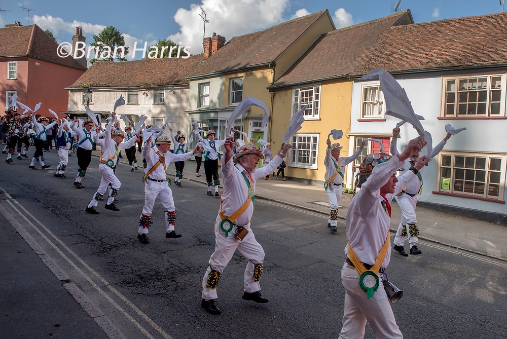Thaxted Morris Weekend, Thaxted Essex England UK. 2-3 June 2018<br /> The 85th Meeting of the Member Clubs of the Morris Ring hosted by Thaxted Morris Men (who wear red and white stripes) who lead the Saturday evening procession to Town Street in Thaxted after a busy day of dancing in a dozen local pubs in surrounding villages in North West Essex. Lincoln and Micklebarrow in yellow and green in Town Street Thaxted.