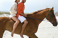 Mid-adult couple riding horse on beach