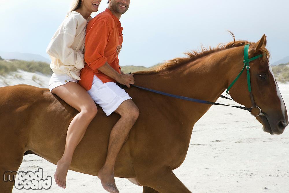 Mid-adult couple riding horse on beach