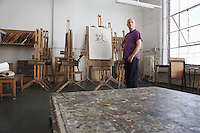 Mature male artist standing by self portrait in art studio