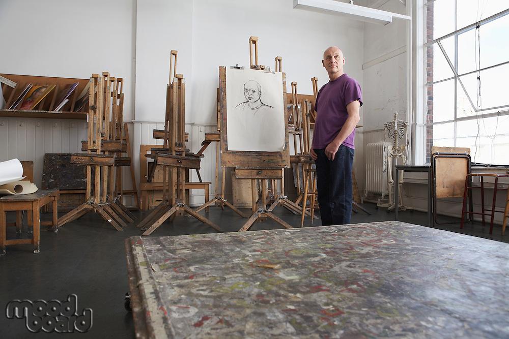 Mature male artist standing by self portrait in art studio