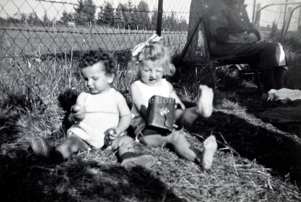two toddlers playing by fence with adult  France 1950s