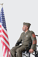 Young US soldier in wheelchair looking at American flag over gray background