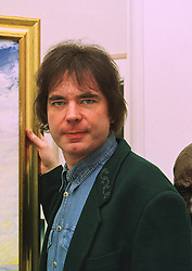 Cellist JULIAN LLOYD WEBBER beside a portrait of himself, at a reception in London on 15th January 1998.MEO 15