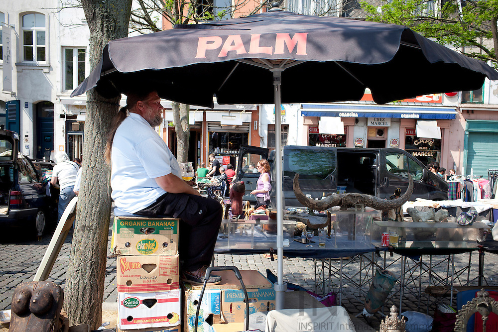 A man with a beer takes shade under his parasol while he waits for customers at the second hand and flea market of the Marolles at Place Jeu de Balle in Brussels Easter Saturday 23 April 2011. Photo: Erik Luntang / INSPIRIT Photo