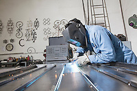 Side view of a young construction worker welding in workshop
