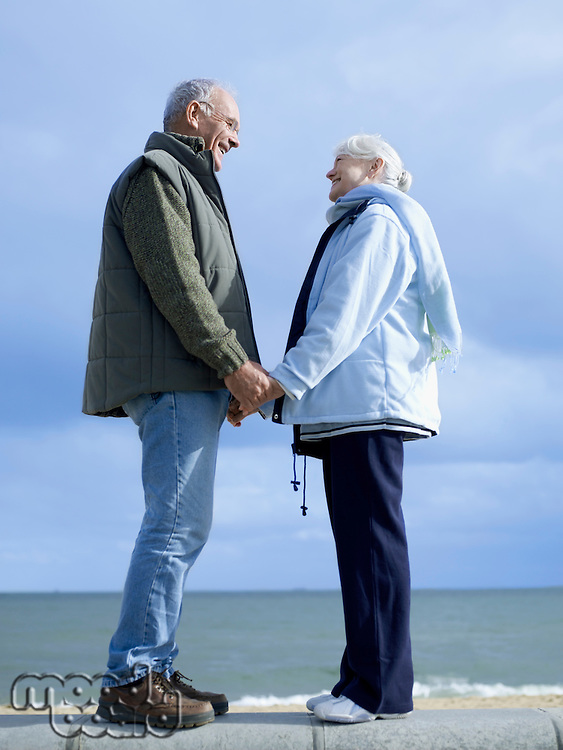Senior couple standing on wall by water holding hands
