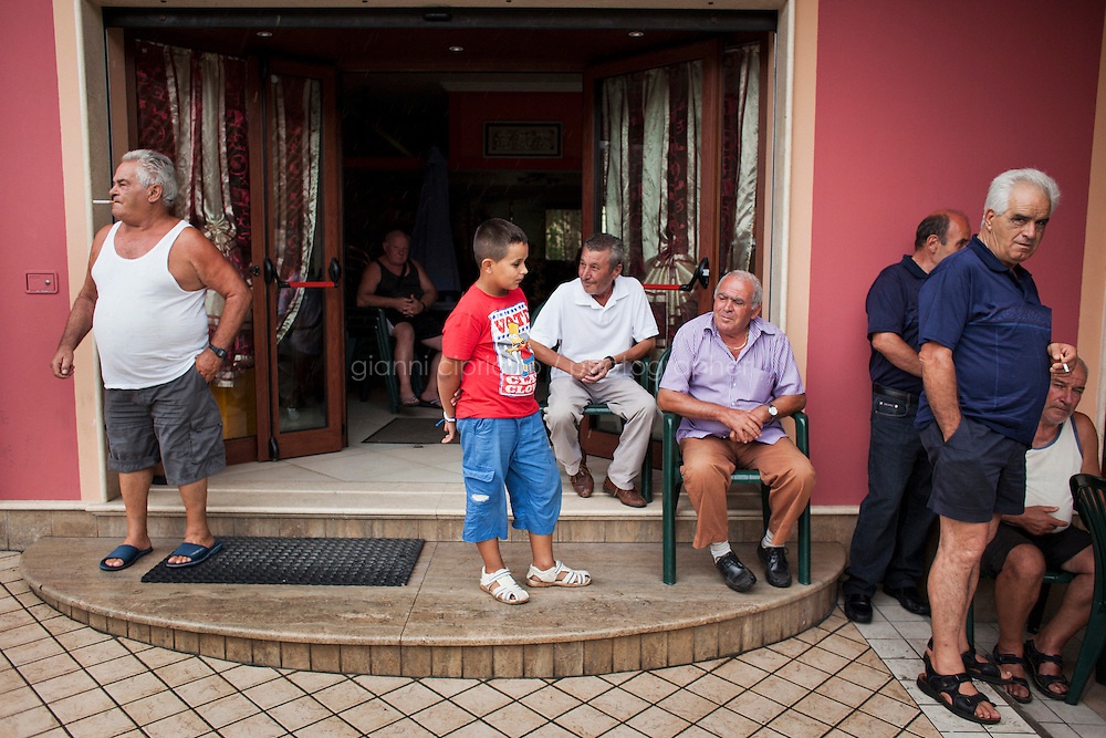 Reggio Calabria, Italy - 1 September, 2012: A young boy stands outside a Cafe with older men in Mileto, Italy, on September 1st, 2012.<br /> <br /> Calabria is one of the poorest Italian regions which suffers from lack of basic services (hospitals without proper equipment, irregular electricity and water), the product of disparate political interests vying for power. The region is dominated by the 'Ndrangheta (pronounced en-Drang-get-A), which authorities say is the most powerful in Italy because it is the welthiest and best organized.<br /> <br /> The region today has nearly 20 percent unemployment, 40 percent youth unemployment and among the lowest female unemployment and broadband Internet levels in Italy. Business suffer since poor infrastructure drives up transport costs.<br /> <br /> Last summer the European Union's anti-fraud office demanded that Italy redirect 380 million euros in structural funding away from the A3 Salerno - Reggio Calabria highway after finding widespread evidence of corruption in the bidding processes.