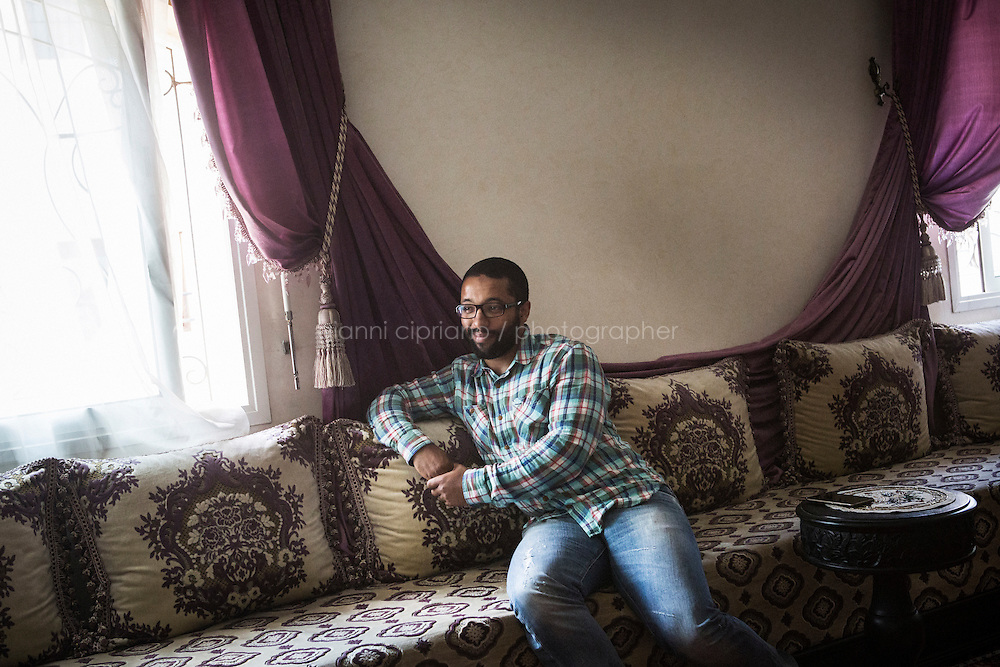 CASABLANCA, MOROCCO - 14 MAY 2016: Ahmed Abdul-Hakeem (28), the son of Luqman Abdul-Hakeem - a close follower of Malcolm X that chauffeured the African American activist around and introduced him to Cuban leader  Fidel Castro in September 1960 - listens to his father during an interview in his home in Sidi Maarouf, a district of Casablanca, Morocco, on May 14th 2016.<br /> <br /> Born in Cleveland, OH, in 1934, Luqman Abdul-Hakeem was raised in Flushing, Queens, and then moved to Bayside, where he graduated in 1952. He attended the New York Technical University for a few months before enrolling in the Navy, where he stayed for two years. Though he had asked for ship duty, he ended up in Springfield, Mass., and Glennclose, Ill. He moved to Brooklyn when his hitch was done and by 1966 was studying jujitsu and aikido. He met Malcolm X during one of his sermons on 116th street in Harlem, New York, in the late 50&rsquo;s. In 1985, Mr. Hakeem decided to move to Marocco because America wasn't a country where he wanted to raise hois children. He has been teaching aikido in the two dojos he owns in Casablanca until 2014, when he underwent a surgery.