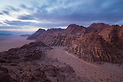 A jeep drives to a remote overlook at dusk in the desert in Wadi Rum, Jordan.
