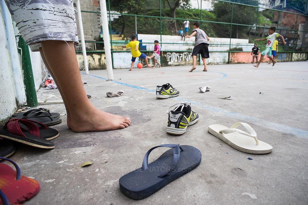 Shoes and flip-flips are discarded as young boys play football barefoot on a concrete football pitch in the Santo Amaro favela, Rio de Janeiro, Brazil. The favela has not been pacified and is one of the less well known of Rio's favelas. A heavily armed police presence was inevidence and there was no trouble of any sort while we were there. According to our guide, Patrick Ashcroft, a teacher and research worker who lives in the favela, violence is rare in this favela. Photo by Andrew Tobin/Tobinators Ltd