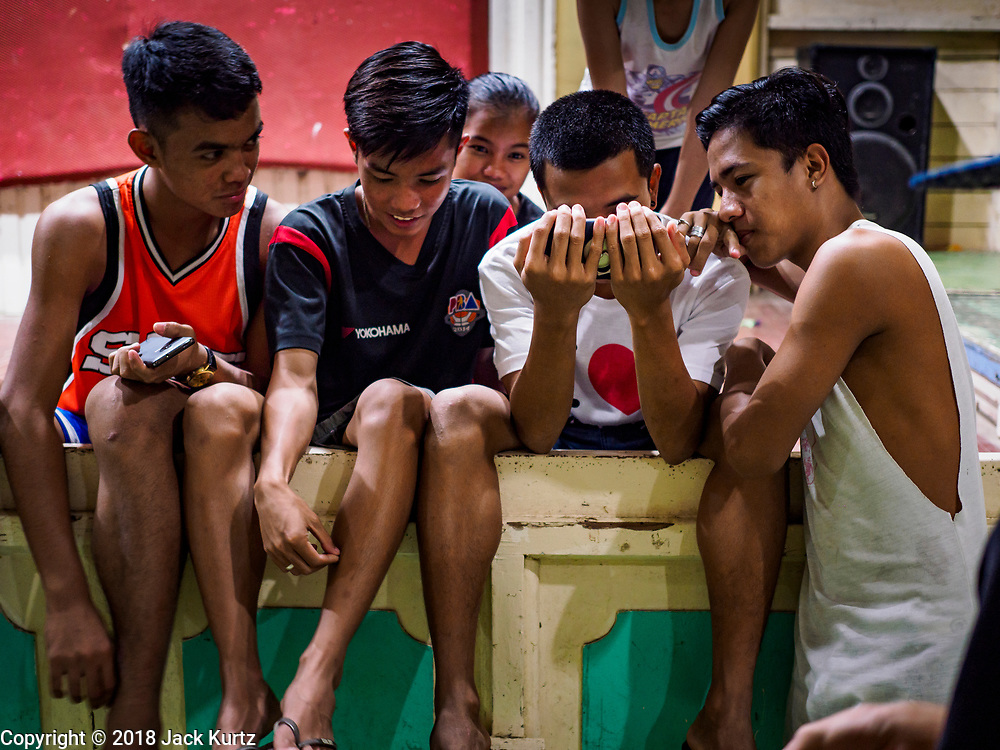 28 JANUARY 2018 - LEGAZPI, ALBAY, PHILIPPINES:  Young men watch a video on a smart phone at the evacuation shelter for people from Barangay (community) Matanag in Albay Central School in Legazpi. People from the community have been in the shelter since Mayon volcano started erupting two weeks ago. There are about 500 families at the shelter, around 2,000 people. More than 80,000 people have been evacuated from communities around the volcano and are living in shelters and camps outside of the evacuation zone. The Philippine government is preparing to house the people for up to three months.     PHOTO BY JACK KURTZ