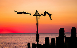 &copy; Licensed to London News Pictures. 03/07/2018. Aberystwyth, UK. A day of unbroken blue skies and searing  heat comes to a beautiful end with people on the seaside pier watching a glorious sunset over Cardigan Bay off Aberystwyth on the west coast of Wales<br /> Photo credit: Keith Morris/LNP