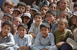 "KABUL,AFGHANISTAN - AUGUST 29: Afghan street children watch a Japanese dancer perform a piece called ""Reconstruction"" at the ASIANA school August 29, 2002 in Kabul Afghanistan.  The Japanese program concluded with 1000 musical instruments donated to the children.  (Photo by Ami Vitale/Getty Images)"