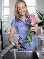 Mid-adult woman rinsing and cutting flowers in kitchen sink