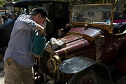 A driver tops-up the radiator of a visiting vintage car in the centre of a French village, during a three-day rally journey through the Corbieres wine region, on 26th May, 2017, in Lagrasse, Languedoc-Rousillon, south of France. Lagrasse is listed as one of France's most beautiful villages and lies on the famous Route 20 wine route in the Basses-Corbieres region dating to the 13th century.