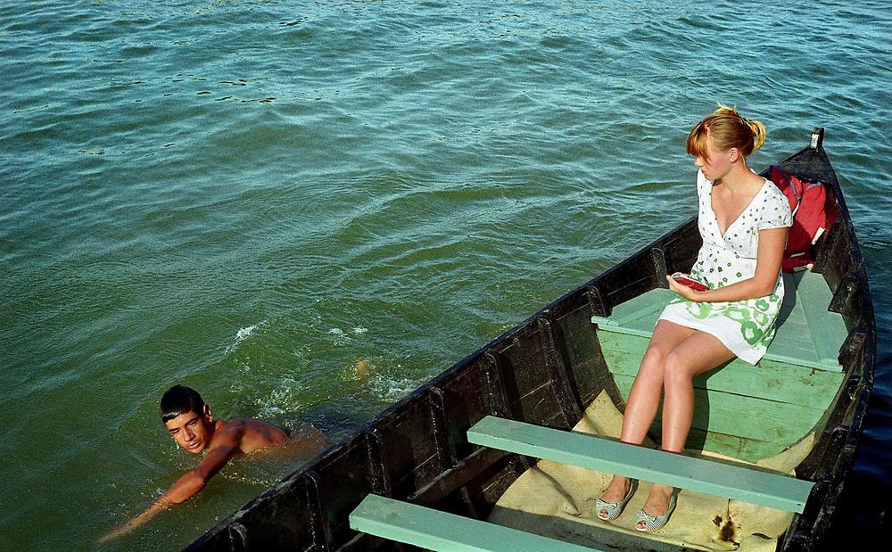 Sulina, a boy swimming next to a boat, Danube Delta, Romania